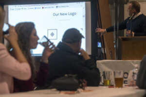 Bruce Gryniewski, of Gallatin Public Affairs, explains his company's re-design of the Port of Centralia logo during the port's 30th anniversary celebration on Thursday at Dick's Brewery in Centralia.